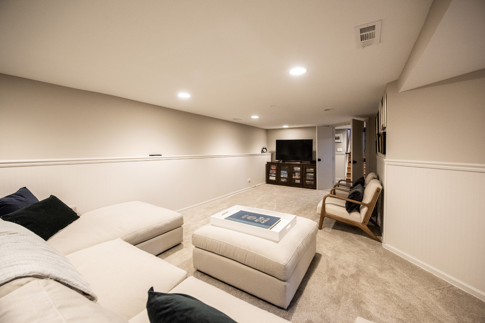 Media Room with white walls a cream sectional and ottoman facing a media stand with a tv on top