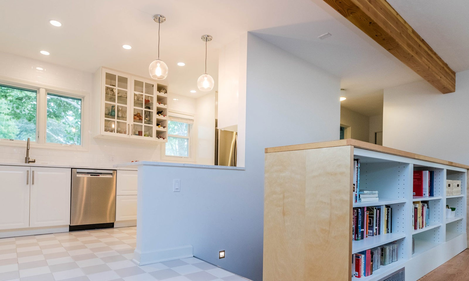 mid century modern ranch renovation and remodel view of stairs down to basement with white kitchen beyond
