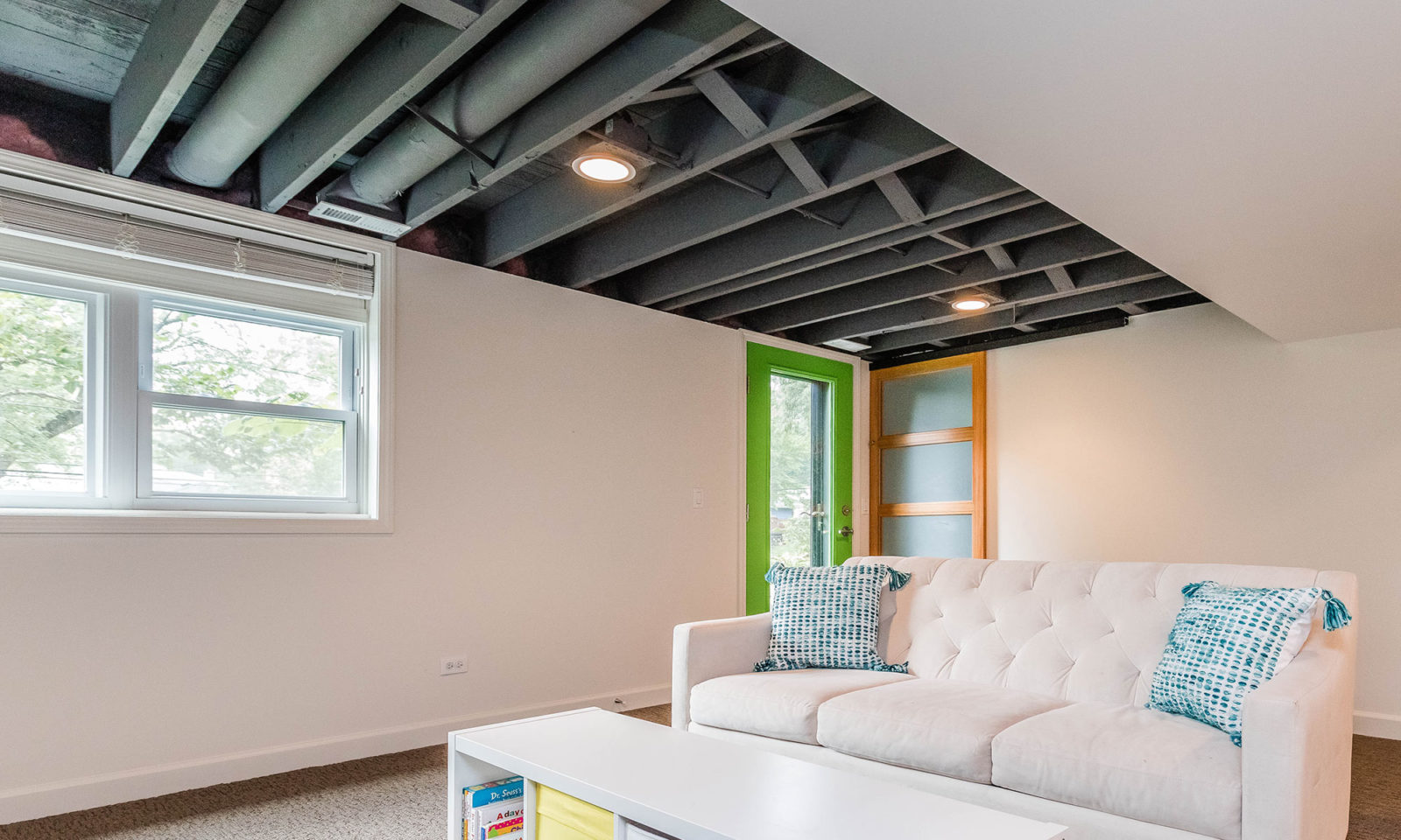 mid century modern ranch renovation and remodel view of finished basement with black painted exposed ceiling joists