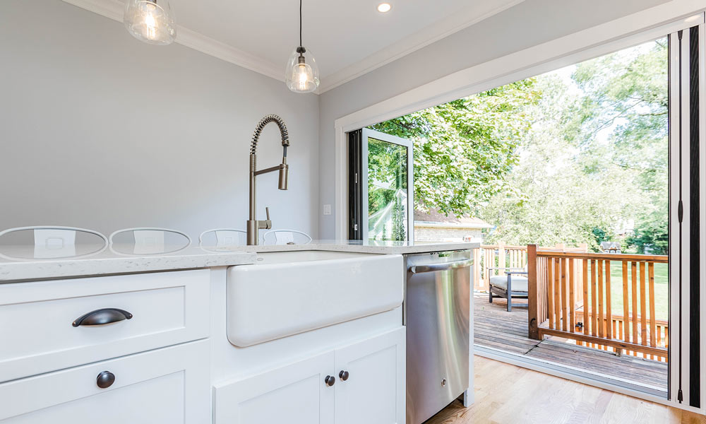 kitchen remodel with folding galss doors to the deck open with accordion screen and farmhouse sink