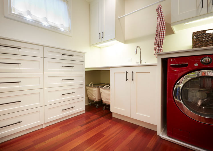 mudroom with white cabinets and 2 drawer sets on hardwood floors and sink next to red clothes washer