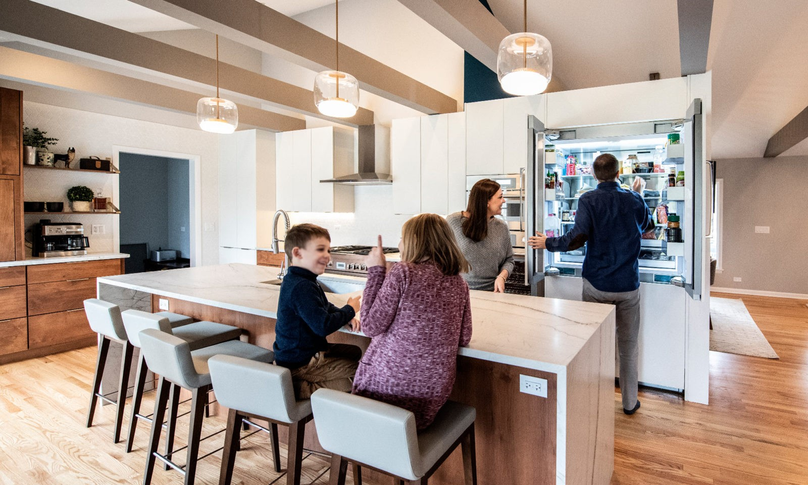 family of 4 in kitchen with large waterfall countertop island white cabinets glass pendant lighting