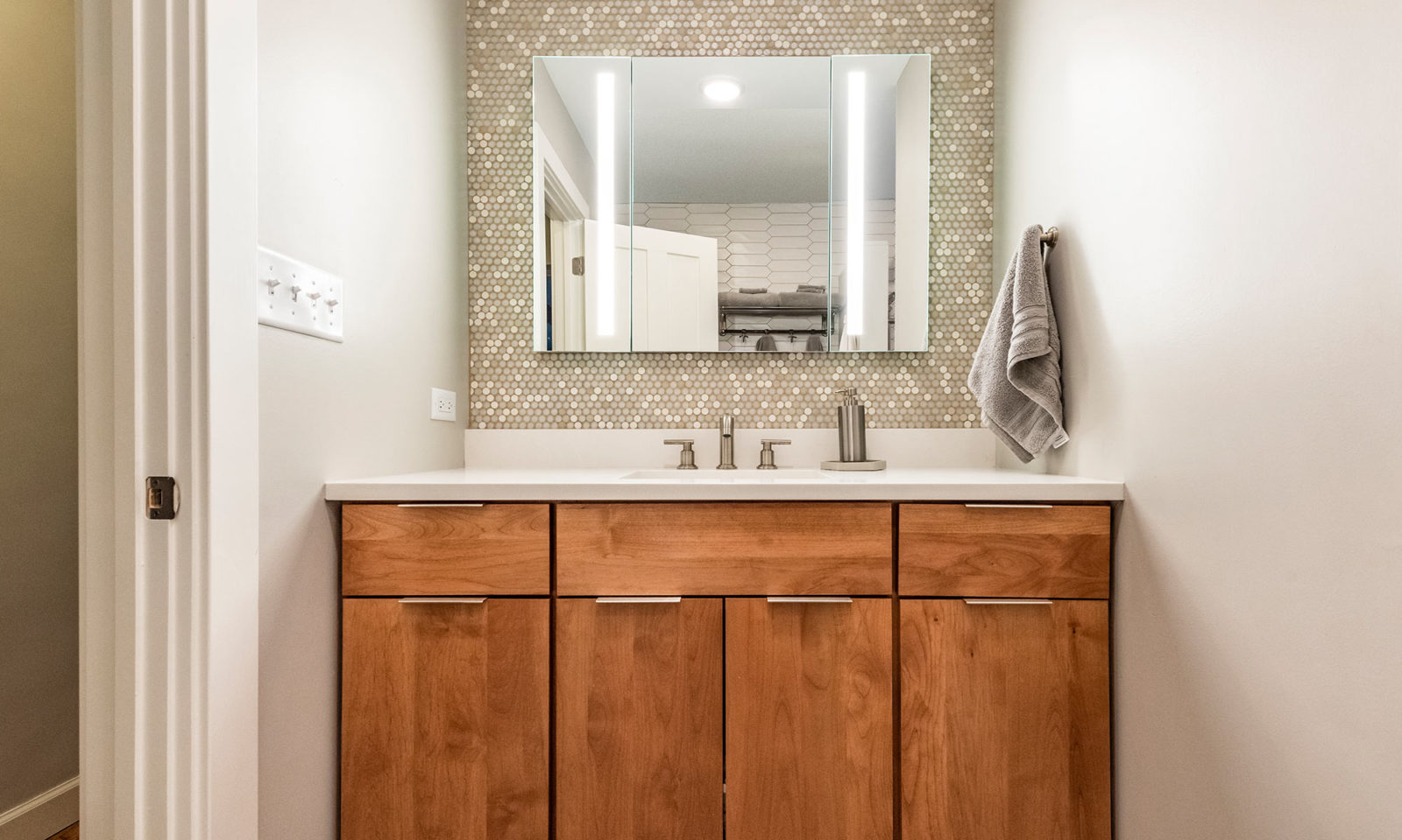 cherry vanity with penny tile backsplash and lighted mirror