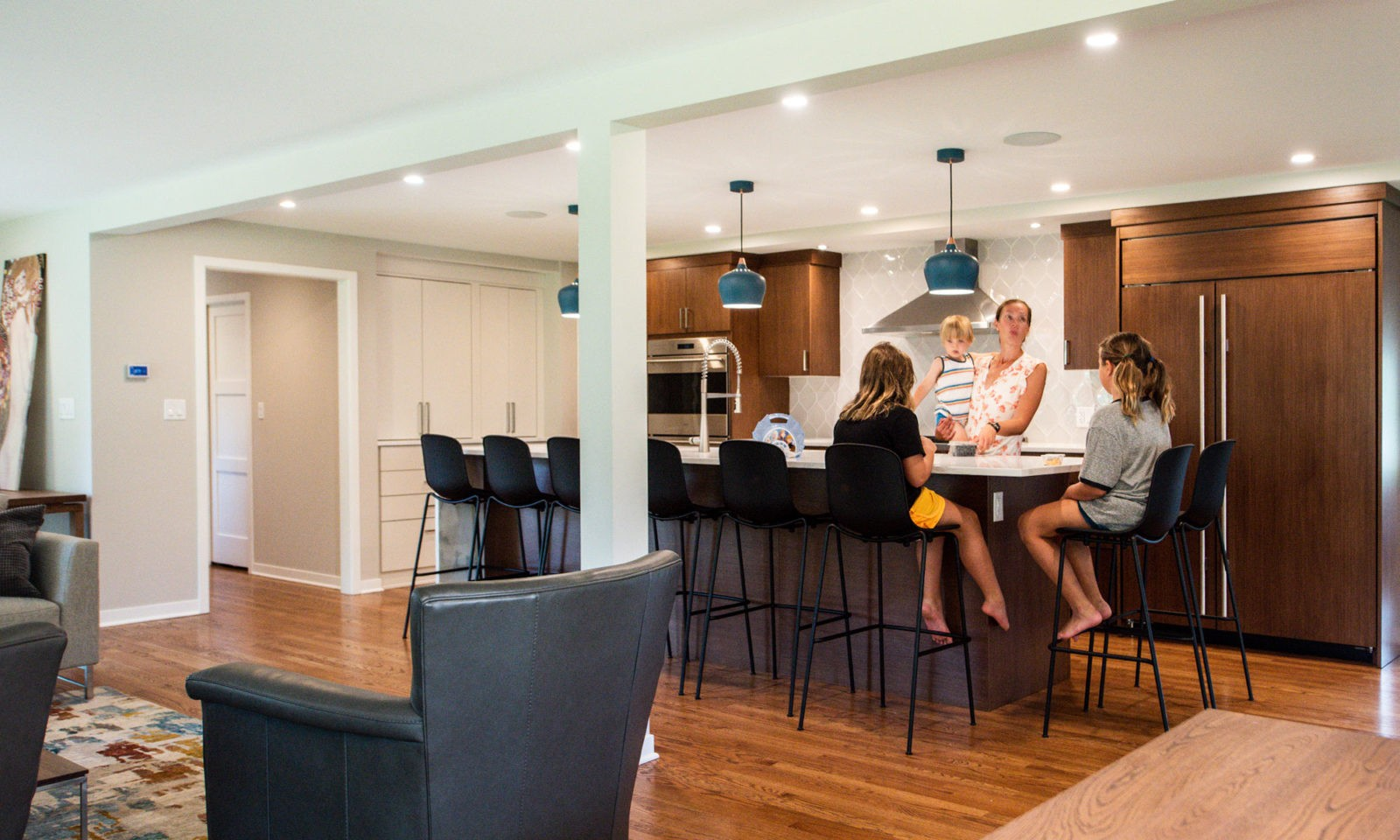 family in a modern hinsdale kitchen remodel with white counters and blue pendant lights