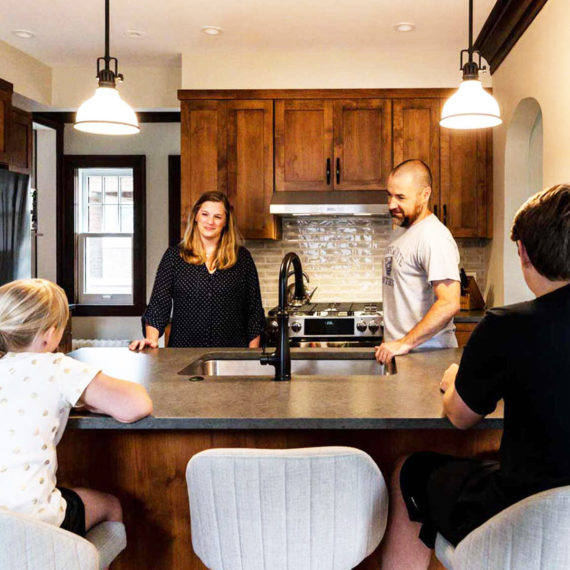 Family gathered in newly remodeled kitchen with dark wood cabinets