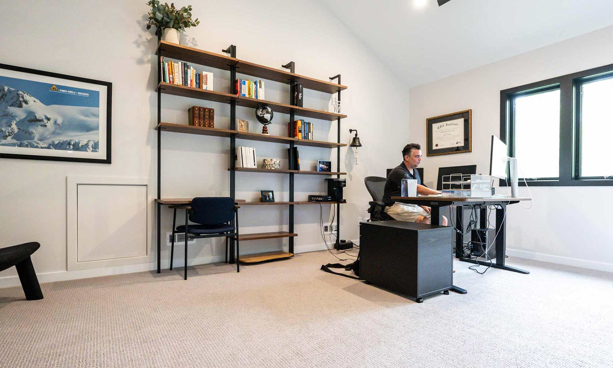 interior view of modern shelves and desk in home office addition with man working